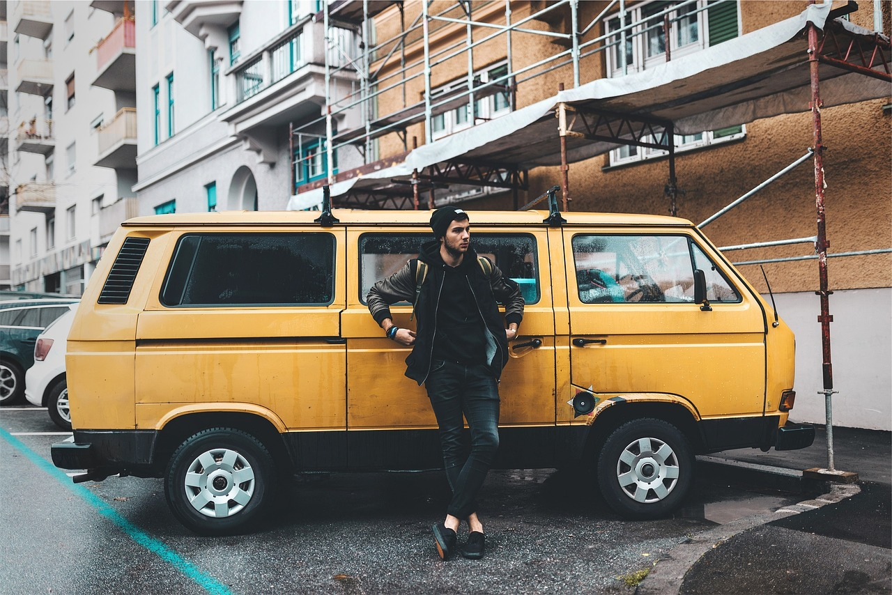 singer in front of a yellow van show in a touring attitude