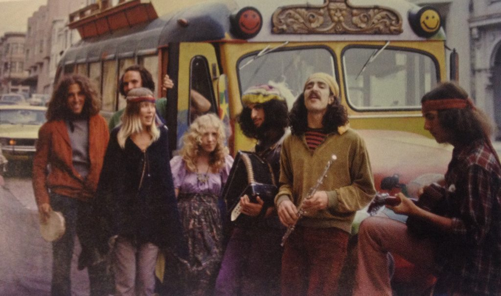 a group of hippies hippies in front of a tour van