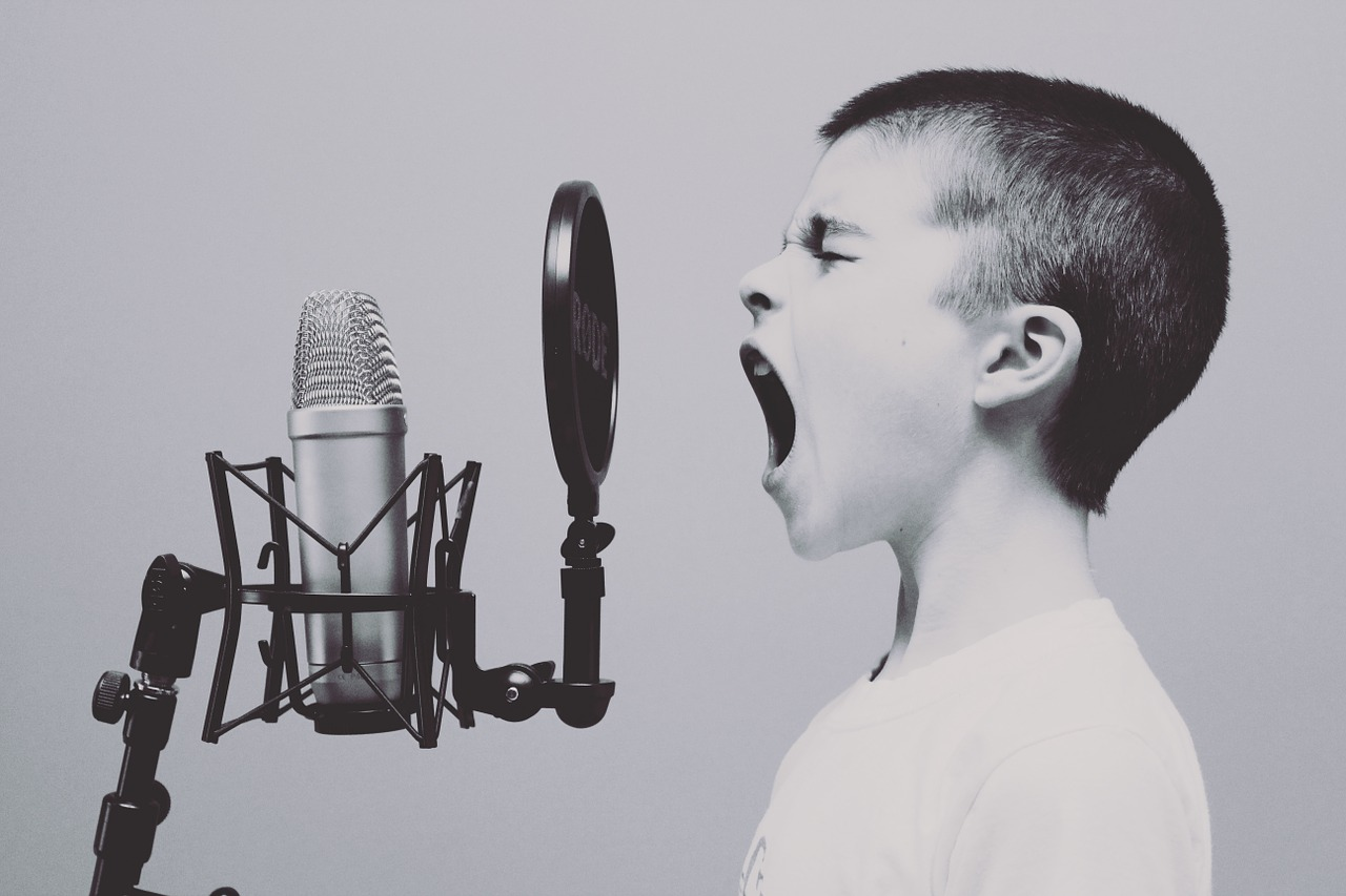 kid singing in front of a microphone